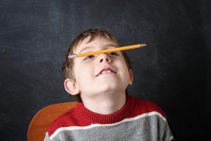 boy balancing pencil on his nose