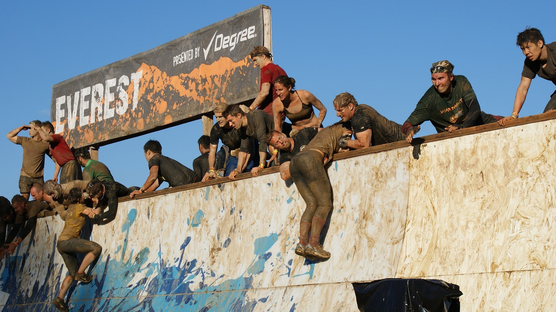 entrants at tough mudder help each other climb a wall