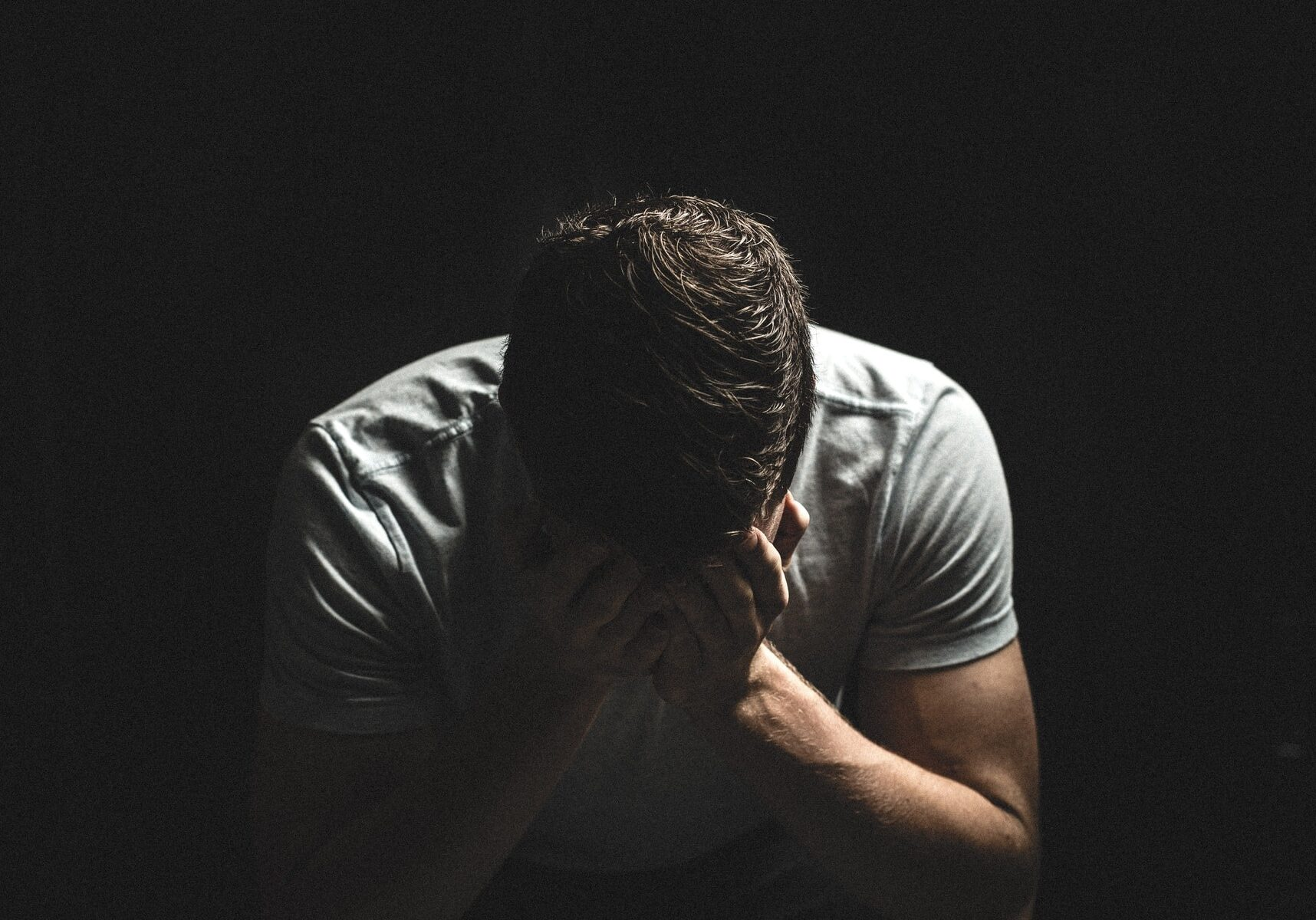 A man with depression, black background, in the dark